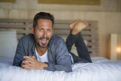 ontspande de jaren '30 gelukkige en knappe mens thuis in toevallige overhemd en jeans die op bed liggen thuis het glimlachen zeke royalty-vrije stock foto's
