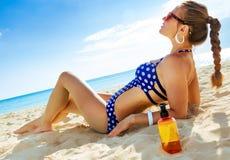 Ontspannen actieve vrouw in swimwear op kust met zonroom stock foto