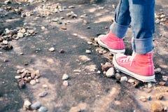 Ontspannen de voeten rode tennisschoen een meisje in aard en tijd Stock Afbeeldingen