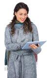 Ontspannen donkerbruine dragende de winterkleren die haar tablet houden Stock Foto