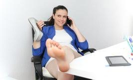 Ontspannen en het winnen bedrijfsvrouwenzitting met haar benen op bureau stock foto's