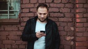 Ontspannen Europese mens die smartphone app buiten gebruiken Knap gebaard mannelijk zakenman mobiel bureau Rode bakstenen muur 4K stock videobeelden