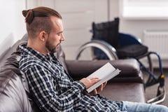 Ontspannen gehandicapte mensenlezing op de laag Stock Foto's