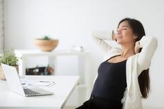 Ontspannen gelukkige Aziatische vrouw die van onderbreking genieten bij werkplaats ademhaling royalty-vrije stock foto's