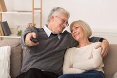 Ontspannen hogere paar het letten op televisie thuis royalty-vrije stock afbeelding