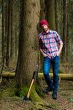 Ontspannen houtvester die met een bijl rusten stock afbeelding