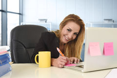 Ontspannen jaren '40vrouw die met blond haar zekere zitting op bureaustoel glimlachen die bij laptop computer werken royalty-vrije stock foto's