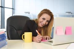 Ontspannen jaren '40vrouw die met blond haar zekere zitting op bureaustoel glimlachen die bij laptop computer werken stock afbeelding