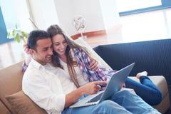 Ontspannen jong paar die aan laptop computer thuis werken stock afbeeldingen