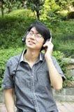 Ontspannen jonge mens die aan muziek op hoofdtelefoon luistert Royalty-vrije Stock Foto