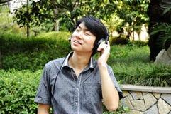 Ontspannen jonge mens die aan muziek op hoofdtelefoon luistert Royalty-vrije Stock Afbeeldingen