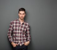 Ontspannen jonge mens met het geruite overhemd stellen Royalty-vrije Stock Afbeeldingen