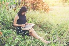 Ontspannen jonge mooie vrouw die een boek lezen bij het gazon met su stock fotografie