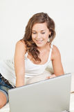Ontspannen jonge vrouw in bed met laptop Stock Foto's