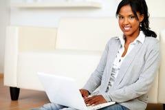 Ontspannen jonge vrouw die bij u met laptop glimlacht royalty-vrije stock afbeelding