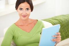 Ontspannen jonge vrouw die een tablet houden Royalty-vrije Stock Afbeeldingen