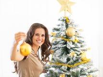 Ontspannen jonge vrouw die Kerstmisbal tonen royalty-vrije stock foto's