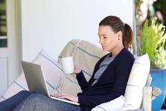 Ontspannen jonge vrouw die laptop thuis met behulp van stock foto's