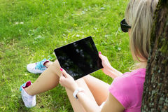 Ontspannen jonge vrouw die tabletcomputer in openlucht met behulp van Stock Afbeelding