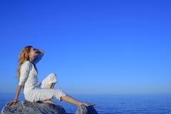 Ontspannen jonge vrouw die van zonsondergang geniet door het overzees Stock Foto's