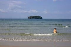 Ontspannen meisje in zeewater door zandstrand Tropische kustmening met eenzame toeristen Enige reiziger op de zomervakantie royalty-vrije stock afbeeldingen