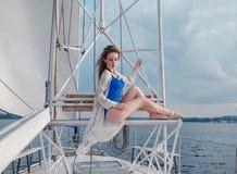 Ontspannen meisjeszitting op zeilboot, die van mild zonlicht, fashi genieten Stock Fotografie