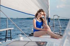 Ontspannen meisjeszitting op zeilboot, die van mild zonlicht, fashi genieten Stock Foto's