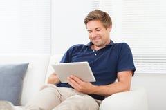 Ontspannen mens die digitale tablet in woonkamer gebruiken Royalty-vrije Stock Foto