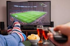 Ontspannen mens die op bank liggen terwijl het letten van op voetbalwedstrijd op televisie, bier en spaanders op lijst stock afbeelding