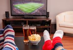 Ontspannen mens die op bank liggen terwijl het letten van op voetbalwedstrijd op televisie, bier en spaanders op lijst royalty-vrije stock afbeelding