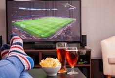 Ontspannen mens die op bank liggen terwijl het letten van op voetbalwedstrijd op televisie, bier en spaanders op lijst royalty-vrije stock fotografie