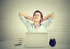 Ontspannen mens met laptop zitting bij de achtergrond van de bureaubakstenen muur royalty-vrije stock fotografie
