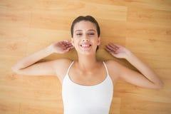 Ontspannen natuurlijke bruine haired vrouw in witte sportkleding die op de vloer liggen Stock Foto
