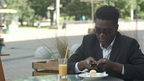 Ontspannen onbezorgde jonge afro Amerikaanse mens in modieuze eyewear zitting alleen bij koffielijst, die slimme telefoon met beh stock videobeelden