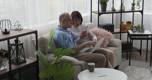 Ontspannen oud paar die laptop op bank in woonkamer met behulp van stock footage