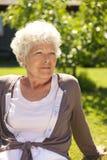 Ontspannen oude damezitting in openlucht royalty-vrije stock fotografie