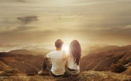 Ontspannen paar die op een zonsondergang letten stock foto's