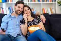 Ontspannen paar het letten op film op de televisie stock fotografie