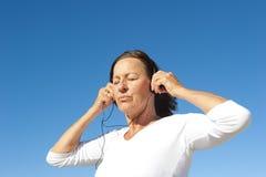 Ontspannen rijpe vrouw met hoofdtelefoons Stock Afbeelding