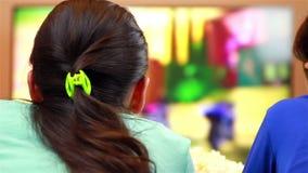Ontspannen tieners die op slimme TV op beeldverhalen letten stock footage