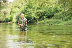 Ontspannen visser die in rivier op een zonnige dag vissen Stock Afbeelding