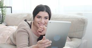 Ontspannen vrouw die digitale tablet op bank thuis gebruiken stock footage