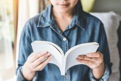 Ontspannen vrouw die een boek op bed in de ochtend lezen, vakantietijd royalty-vrije stock afbeeldingen