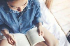 Ontspannen vrouw die een boek op bed in de ochtend lezen, vakantietijd stock afbeeldingen