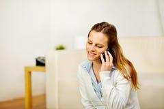 Ontspannen vrouw die een mobiele telefoon thuis met behulp van stock foto's