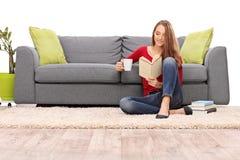 Ontspannen vrouw die van een koffie genieten en een boek lezen Stock Afbeeldingen