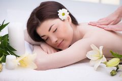 Ontspannen vrouw met bloemen in kuuroordcentrum het genieten van Royalty-vrije Stock Afbeeldingen