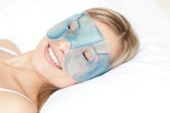 Ontspannen vrouw met een masker van het ooggel royalty-vrije stock foto