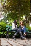 Ontspannen vrouwelijke vrienden die in het park babbelen royalty-vrije stock afbeelding