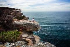 Ontspannen vrouwenzitting op kustlandtong die uit aan oceaan kijken royalty-vrije stock afbeelding